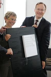 Regierungspräsident Johannes Schmalzl (re.) übergibt die Auszeichnung an Mediathek-Leiterin Ursula Jaksch.