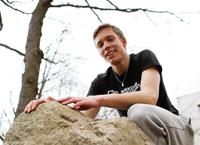 HdM-Student Elmar Schaaf posiert auf einem großen Hinkelstein.
