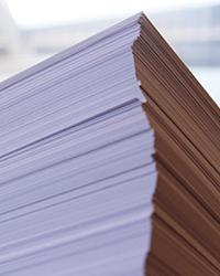 US-Künstler Goldsmith liest einen rund zwei Meter hohen Papierstapel mit Interausdrucken vor.