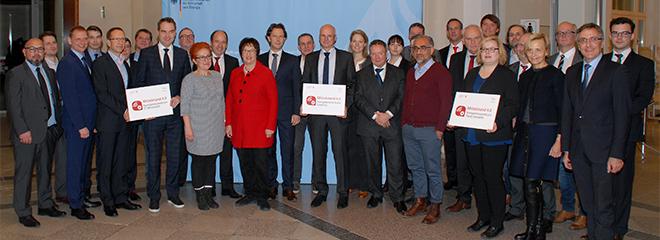 Brigitte Zypries, Bundesministerin für Wirtschaft und Energie (Mitte), Prof. Dr. Michael Burmester (mit Schild, Mitte) und Dr. Katharina Zeiner (rechts neben Prof. Dr. Michael Burmester), Foto: BMWi/Andreas Mertens